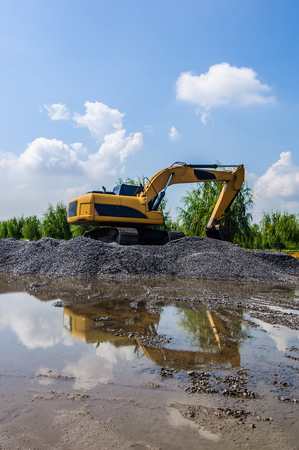 Backhoe standing on stone on construction site. Stock Photo