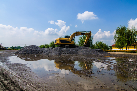 dredging tools: Backhoe standing on stone on construction site. Stock Photo