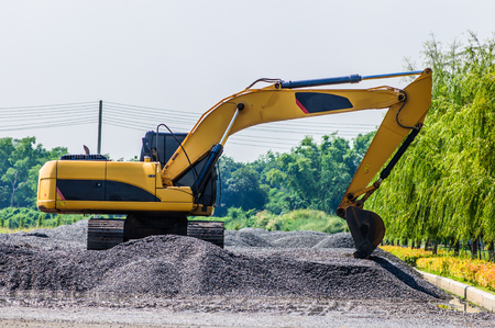 dredging tools: Backhoe standing on stone on construction site