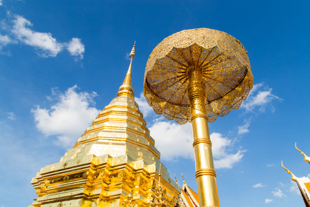 Golden Buddhas relics and pagoda on sunny and blue sky , they are in area of the public temple in Thailand.