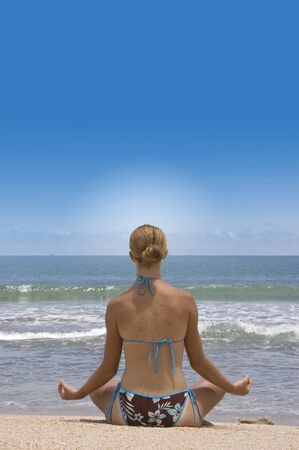 attractive young woman in yoga pose at the beach photo