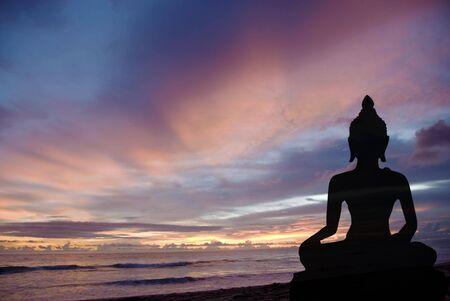 thai yoga: Silhouette of Buddha during sunset at the beach
