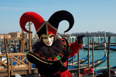 carnivale: Black and red jester in front of gondolas on Grand Canal,Venice,Italy