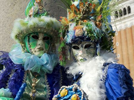 two party goers in St Marks Square,Venice,Italy dressed up in costume featuring seashells