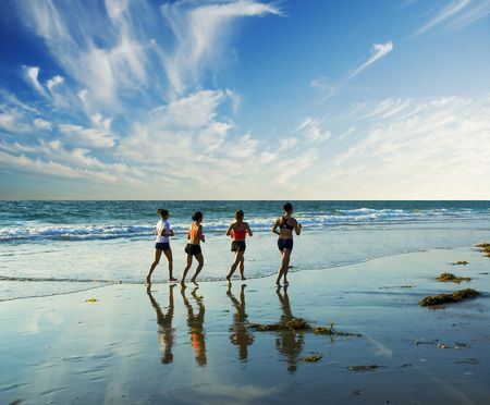 bare feet boys: four women go jogging on the beach along the waters edge