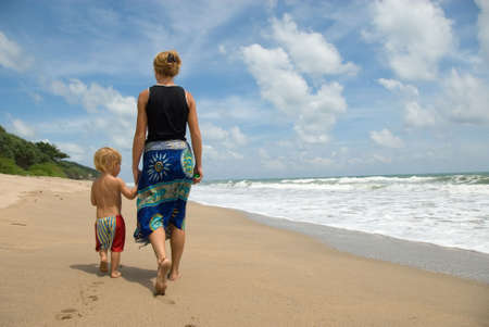 mother and child walking at the beach photo