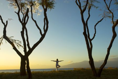 silhouette of woman practicing yoga at sunset on the Island of Maui in Hawaii photo