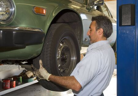 serviceman: a mechanic is changing a tire on a automobile