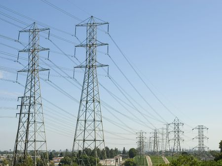 over voltage: a group of high voltage power towers and electrical lines going over a hill from the power station