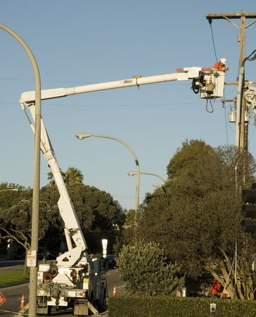 utility pole: blue collar utility pole worker installing new wires and cables on power utility pole