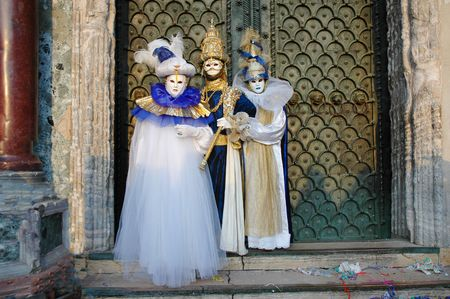 saint mark's square: three costumed people going to mardi gras carnivale in Venice Italy and standing in Saint Marks square