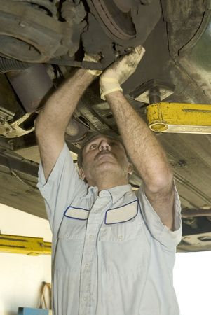 auto repair mechaic inspects the undercarriage of an automobile photo