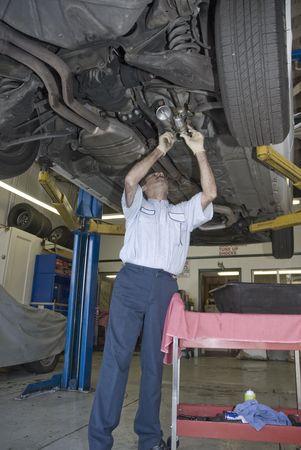 automobile mechanic inspects under a car photo