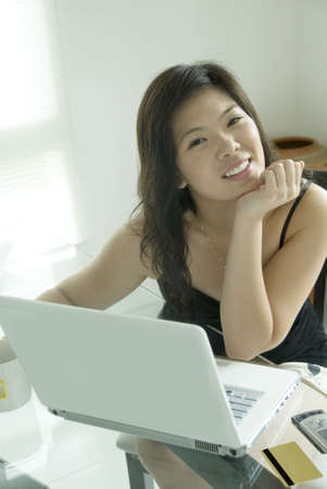 Pretty Asian woman with notebook computer sitting at table photo