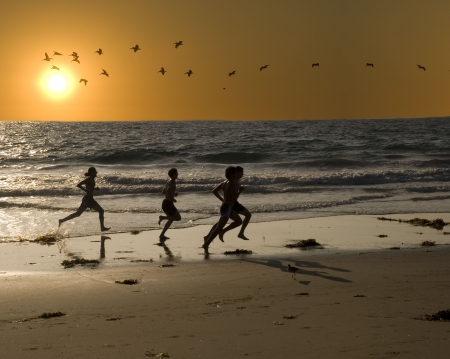 keep: a group of young men are exercising by jogging on the beach for fitness