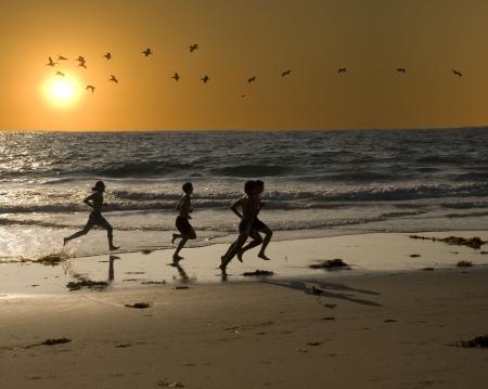 ni�o corriendo: un grupo de hombres j�venes son el ejercicio de jogging en la playa de aptitud