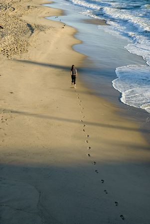 woman walking alone on the beach   photo
