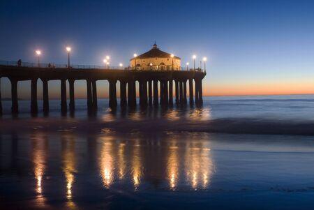 A pier extending into the Ocean atlow tide in Manhattan Beach,California photo