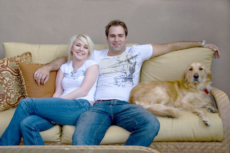 animal watching: young couple with their dog sitting on couch