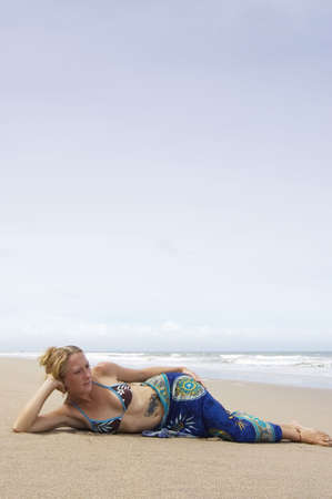 lonliness: attractive young woman laying on the beach