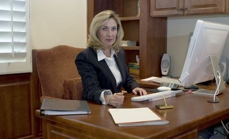 Female executive sitting at her desk offering a pen to sign a document Stock Photo - 2362485