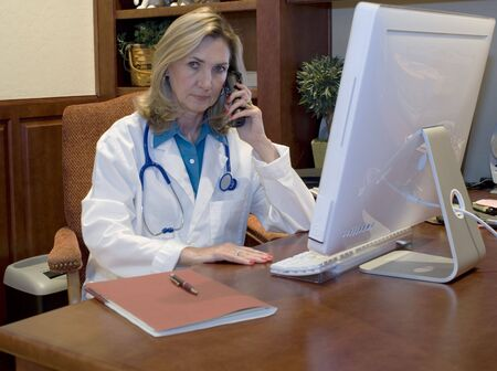 Female Doctor talking on phone in her office