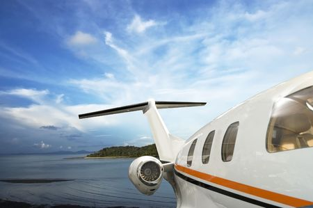 private plane: private jet flying over tropical Island