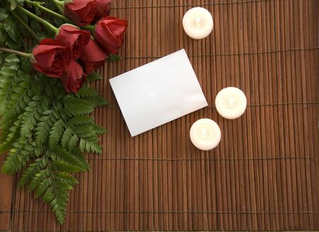 red roses on bamboo with candles and notecard photo