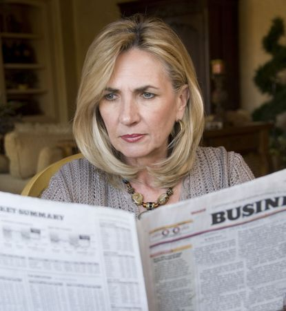 Mature woman reading the financial news photo