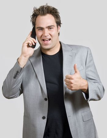 confident young man with mobile phone and thumbs up Stock Photo - 2731469