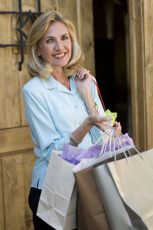 Mature woman returning home from shopping with her bags photo