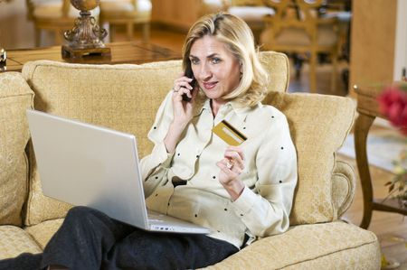 Mature woman shopping at home online with computer and credit card. photo