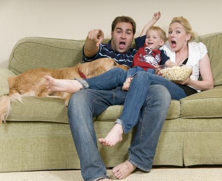 animal watching: young family watching movie at home