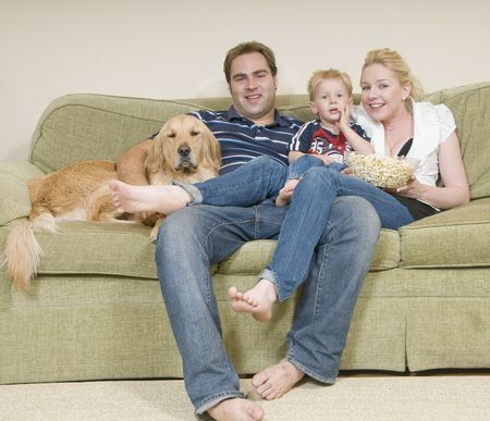 woman couch: young family sitiing on sofa and eating popcor Stock Photo