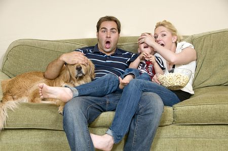 young family watching movie at home and hiding eyes