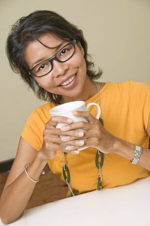 Modern Asian woman relaxing with a cup Stock Photo - 3535328