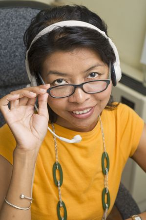 Attractive Asian business woman wearing headset and smiling Stock Photo - 3535329