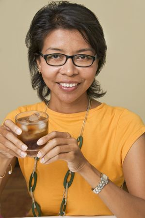 Modern looking Asian woman holding a drink and looking at camera photo