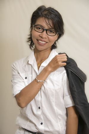 Modern looking Asian woman standing with her jacket over her shoulder photo