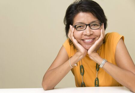 Modern looking Asian woman resting her head on her hand and looking at camera photo