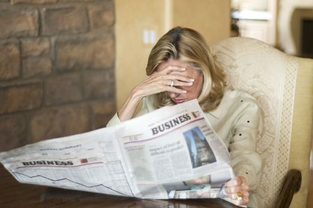 housing crisis: Mature woman reading the financial news