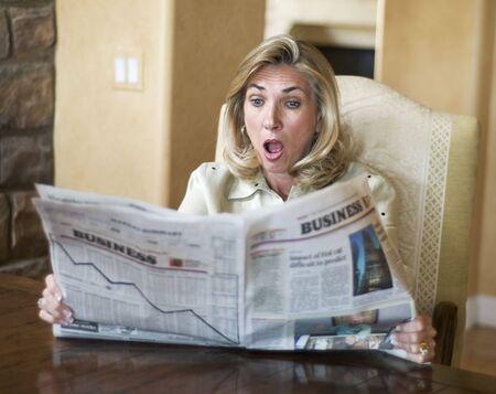 meltdown: Mature woman reading the financial news