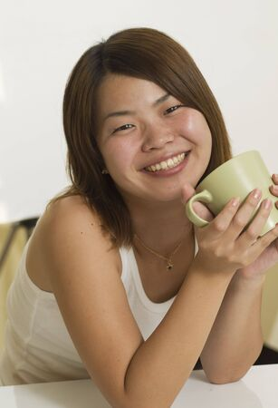 Beautiful young Asian woman having a cup of tea Stock Photo - 3757563