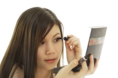 Attractive young Asian girl putting on makeup Stock Photo - 3895524