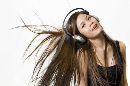 Sexy young Asian girl listening to music on headphones photo