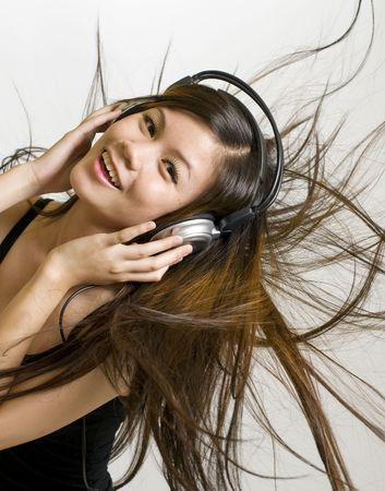 Sexy young Asian girl listening to music on headphones