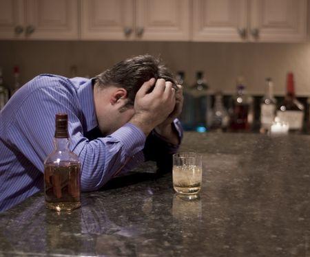 oscuro retrato de un hombre con la cabeza en la desesperación y con una bebida alcohólica Foto de archivo