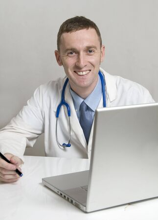 Handsome young Doctor with computer at his desk Stock Photo - 4572570