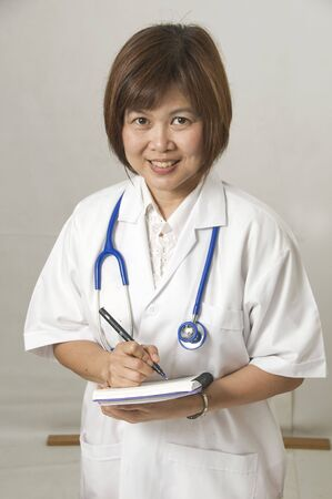 Asian nurse standing and writing in patients records Stock Photo - 4582774