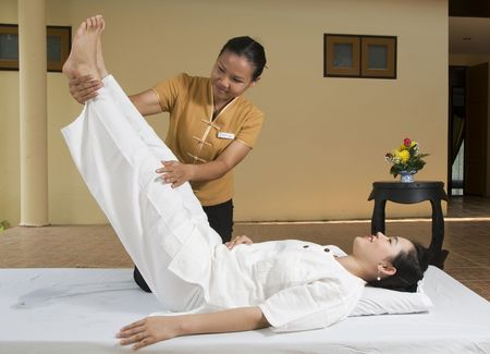 thai massage: Woman getting Thai massage from professional masseuse Stock Photo